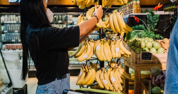 woman with face mask holding yellow banana fruit