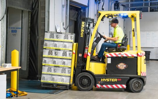 man riding a yellow forklift lifting boxes